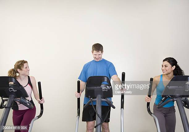 Three adults on elliptical trainers in gym, smiling