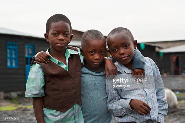 Three african boys in the destroyed town of Goma, Congo