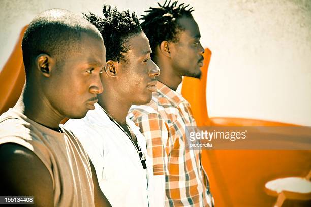 Three Africans Men In A Row, Looking At Horizon