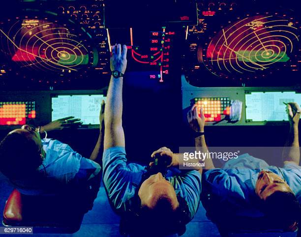 Three Air Controlmen monitor incoming aircraft in the carrier air traffic control center aboard the nuclearpowered aircraft carrier USS Abraham...