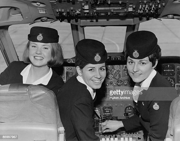 Three air hostesses in the cockpit of an airliner circa 1965