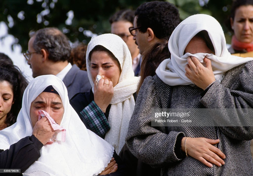 Three Algerian women mourn victims killed in the Algiers Riots of October 1988. Mourners gathered in December for a prayer service in honor of the hundreds of protesters killed by government troops during the anti-government riots.
