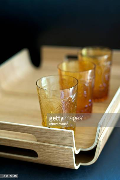 Three amber drinking glasses on wooden tray