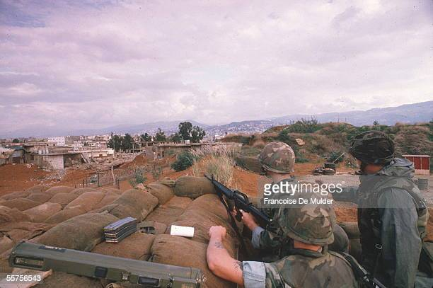 Three American Marines in a sandbag emplacement keep a close eye on two Lebanese civilians nearby in a group of ruined buildings beside the Americans...