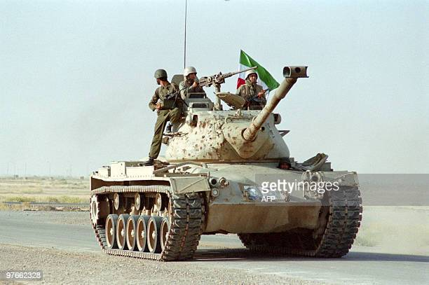 Three antiKhomeini Iranian National Liberation Army soldiers practice manoeuvres on a captured US tank used by Khomeini army on May 31 1988 near the...