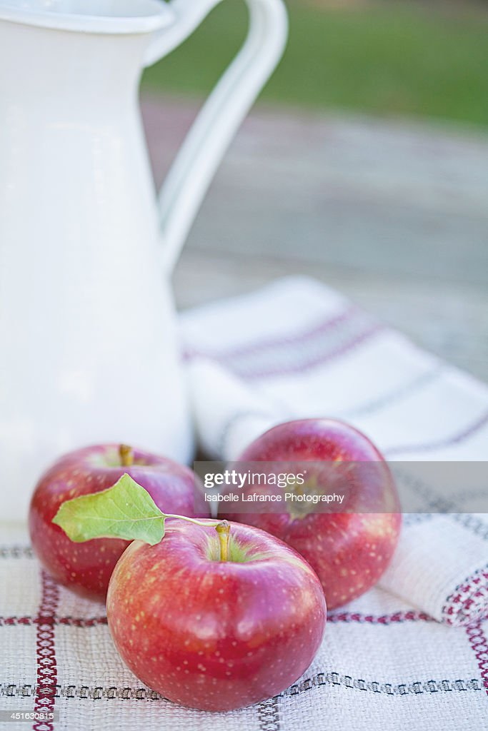Three apples and a white pitcher : Stock Photo