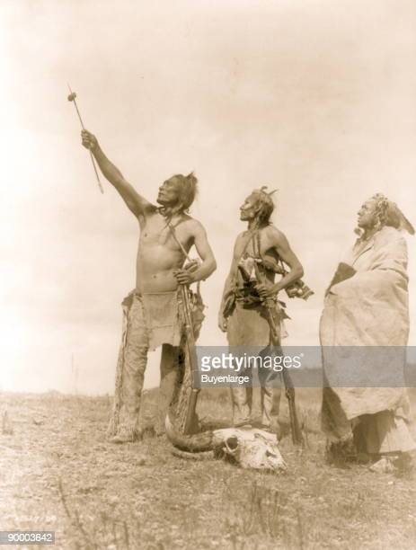 Three Apsaroke men gazing skyward two holding rifles one with object skewered on arrow pointed skyward bison skull at their feet