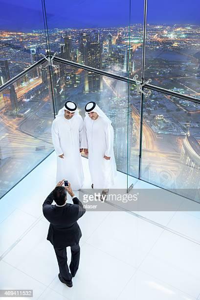 Three arab business men taking a picture, Dubai skyline