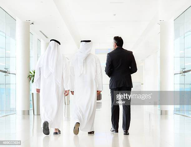 Three arab business men walking, talking, meeting