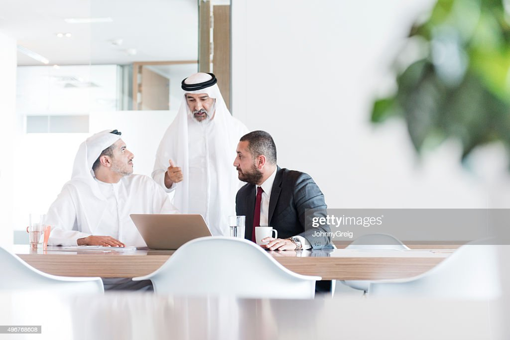Three Arab businessmen in business meeting in modern office