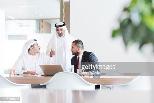 Three Arab businessmen in business meeting in modern office
