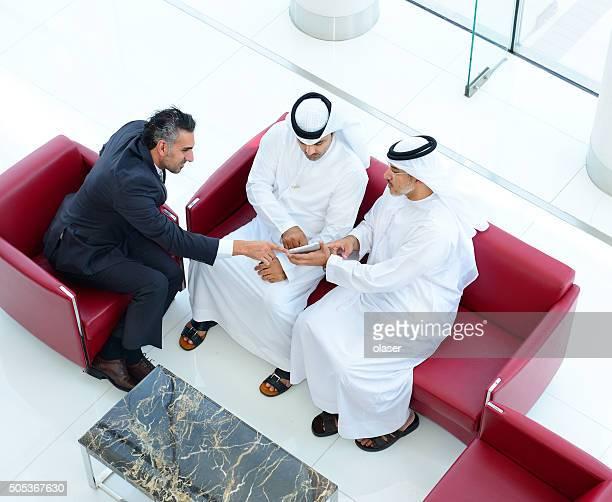 Tres hombres de negocios árabe en reunión, con comprimidos y teléfonos