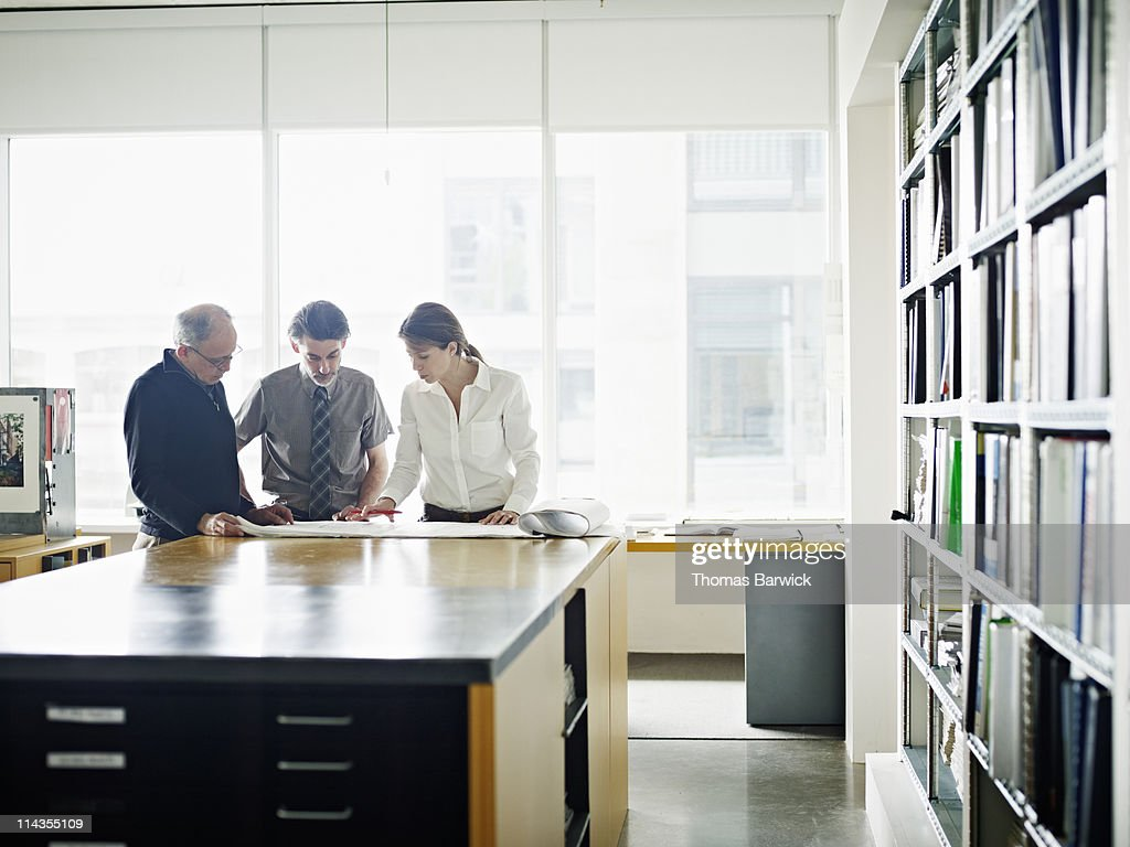 Three architects examining plans at desk in office : Stock Photo