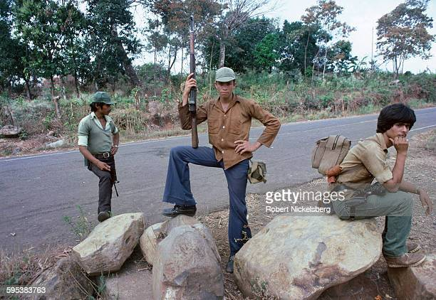 Three armed People's Revolutionary Army guerrillas pose beside a highway in southeastern El Salvador February 1 1983 At the time the country was...