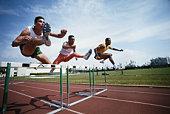 Three athletes jumping hurdle