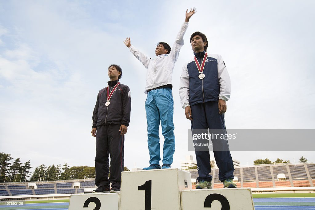 Three athletes on podium with medals