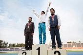 Three athletes on podium with medals
