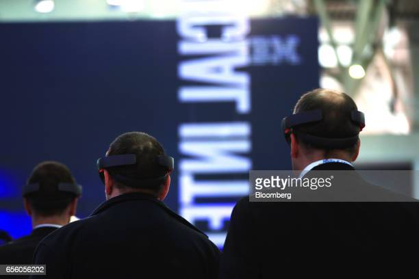 Three attendees test augmented reality headsets at the CeBIT 2017 tech fair in Hannover Germany on Tuesday March 21 2017 Leading edge technologies in...
