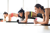 Three attractive sport girls doing plank exercise lying on yoga mat in fitness class.