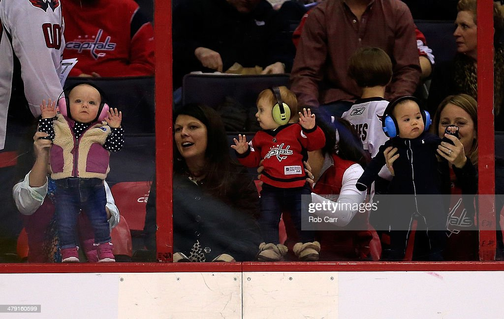 Three babies look on from behind the glass before the start of the Washington Capitals and Toronto Maple Leafs game at Verizon Center on March 16, 2014 in Washington, DC.