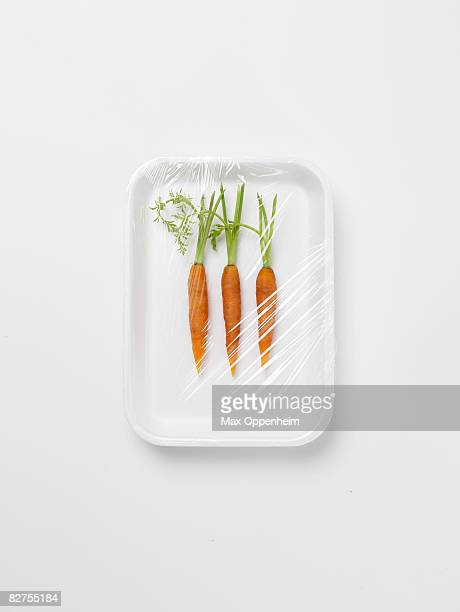 three baby carrots encased in plastic wrapping