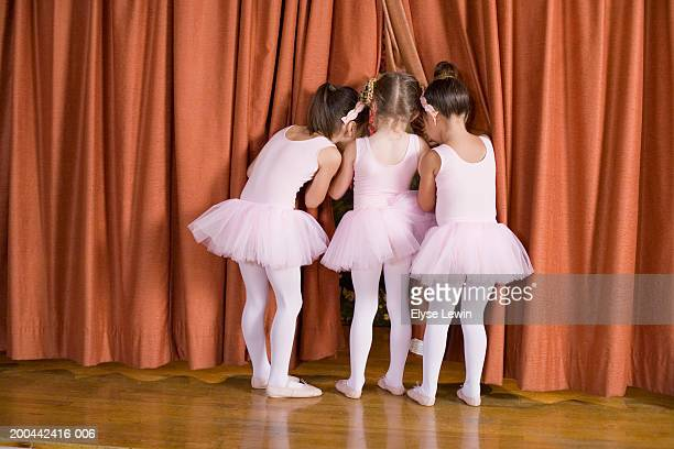 Three ballerinas (5-7) peeking out from behind curtain, rear view