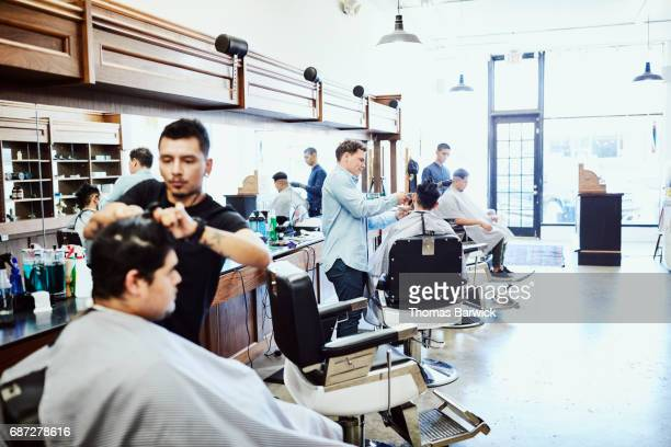 Three barbers working on clients hair in barber shop