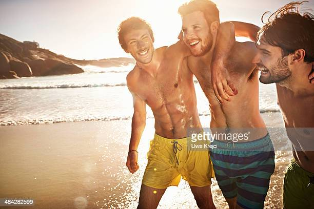 Three bare-chested men on beach, smiling, close-up