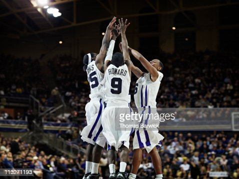 Three basketball players celebrating in arena : Stock Photo