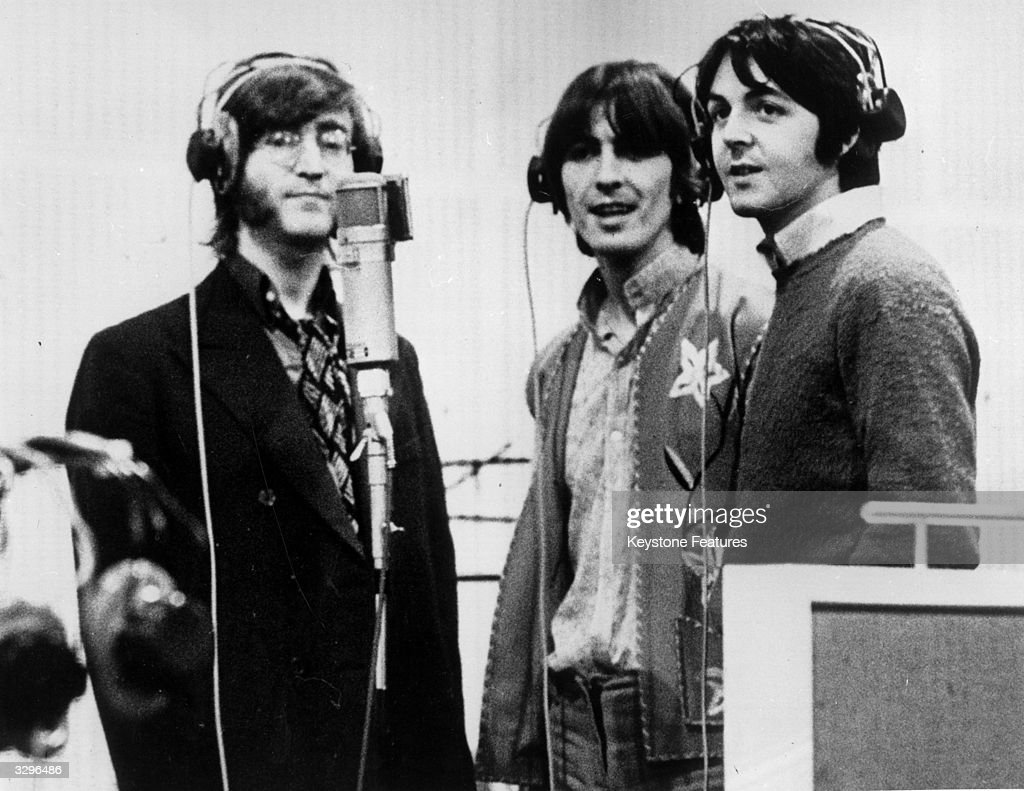 Three Beatles; from left to right John Lennon (1940 - 1980), George Harrison (1943 - 2001) and Paul McCartney, record voices in a studio for their new cartoon film 'Yellow Submarine'.
