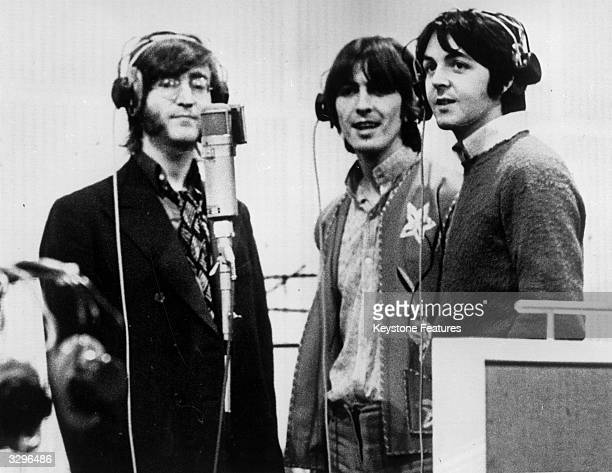 Three Beatles from left to right John Lennon George Harrison and Paul McCartney record voices in a studio for their new cartoon film 'Yellow...