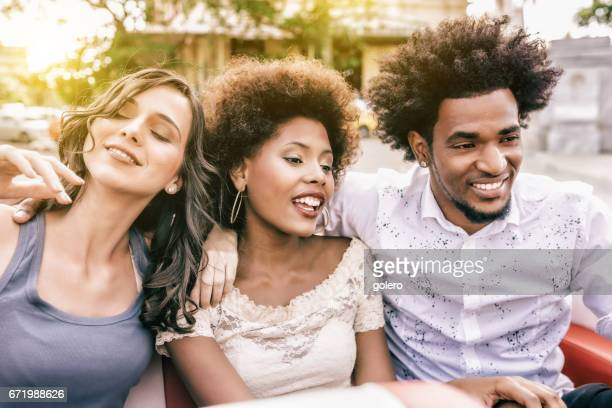 three beautiful young cuban people cheering in cabrio car in Havanna