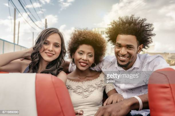 three beautiful young cuban people relaxing in cabrio car in Havanna
