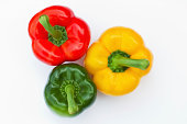 three bell peppers in red, green and yellow on white background