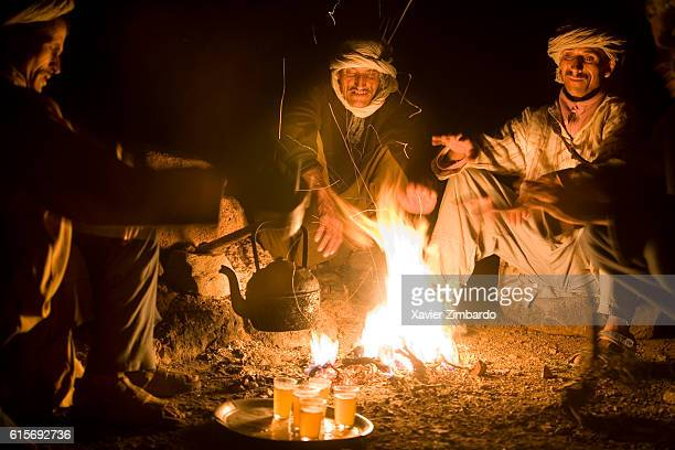 Three Berber shepherds warm their hands over an open camp fire on May 16 2007 in Atlas Mountains Morocco