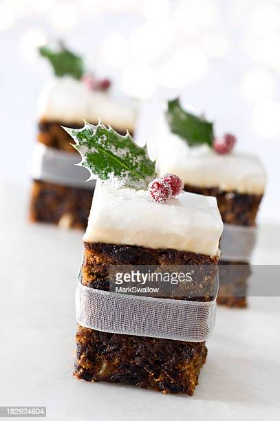 Three bite sized pieces of Christmas cake isolated on white