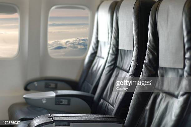 Three black aircraft seats looking out of the window