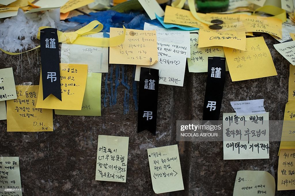 Three black ribbons with the inscription 'rest in peace' are seen at a makeshift memorial at the main gate of Danwon High School in Ansan on April 25, 2014. The confirmed death toll stood at 171, but 131 were still missing as dive teams searched in near pitch-black conditions for bodies trapped in the ferry's interior. AFP PHOTO/ Nicolas ASFOURI