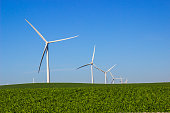 Three Bladed Energy Producing Windmills In Open Field