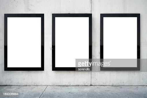 Três Quadros para cartazes em branco na parede.