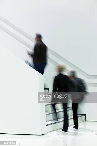 Trois personnes floues à pied'escalier blanc