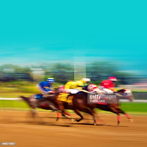Three blurred racehorses on a dirt track