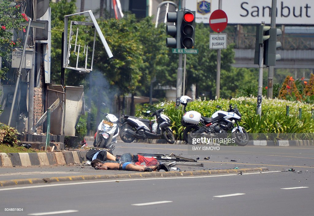 TOPSHOT Three bodies lie on the street next to a damaged police post after a series of blasts hit the Indonesia capital Jakarta on January 14 2016 A...
