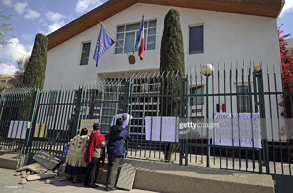 Three Bolivians hang placards with texts of protest on the fence of the French embassy in La Paz on June 3, 2013. Bolivian officials accused France, Portugal, Italy and Spain of denying entry to the jet late Tuesday over 'unfounded rumors' Snowden was traveling on board. AFP PHOTO/JORGE BERNAL