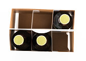 Pattern of three beer bottles in six pack cardboard container with gold caps facing upwards
