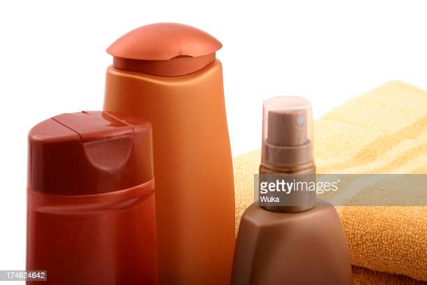 Three bottles of plastic cosmetics and a towel