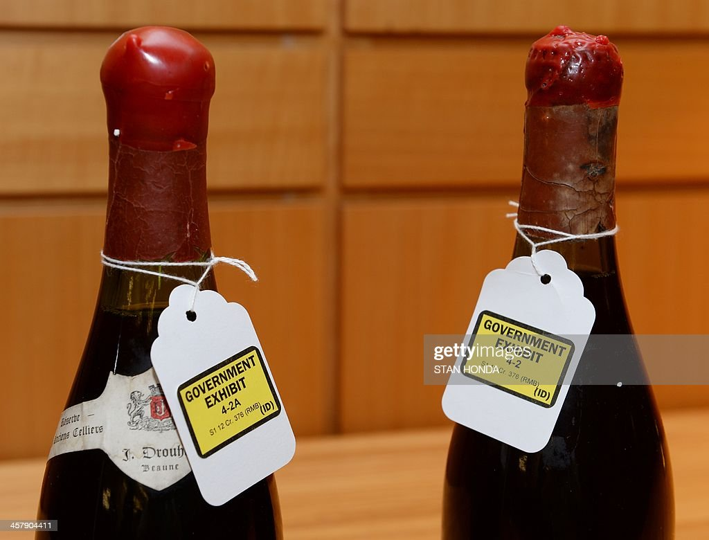 Three bottles of wine used as evidence in the trial of wine dealer Rudy Kurniawan are displayed in Federal Court on December 19, 2013 in New York. Kurniawan was found guilty of masterminding a lucrative scheme to sell fake vintage wine in New York and London. AFP PHOTO/Stan HONDA