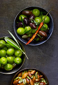 Three bowls of marinated olives and spiced nuts.
