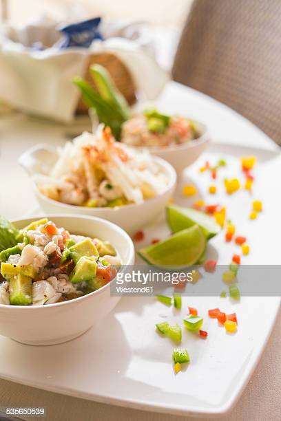 Three bowls of marinated raw seafood with a mix of fresh vegetables