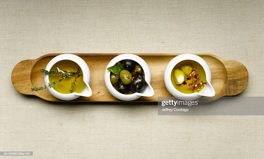 Three bowls with olives, herbs and oil, studio shot : Stock Photo